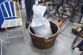 Half barrel planter and a bag of rubberised/chopped up tyres