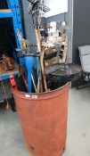 Large metal incinerator with a quantity of garden tools including strimmer, forks, sieves, rakes,