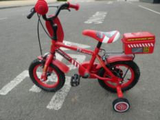 Red small Fireman Sam childs bike with stabilisers