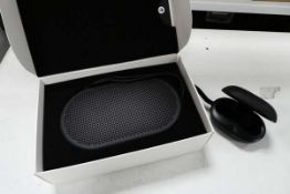 Bang & Olufsen P2 portable bluetooth speaker along with a Bang & Olufsen E8 wireless charging case