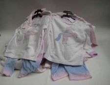 Bag containing children's 3 piece pyjamas sets decorated with a unicorn