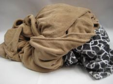 Bag containing 2 throws, 1 in grey with geometric pattern and 1 in camel colour