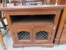 Stained pine side table with 2nd tier and metal lattice work doors under