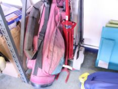 Red Titleist golf bag with small quantity of various clubs and manual trolley