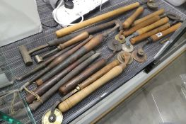 A collection of wooden handled plain and patterned roller knurling tools, blocks and hammer