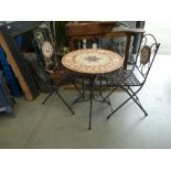 Small tile topped round garden table and two chairs