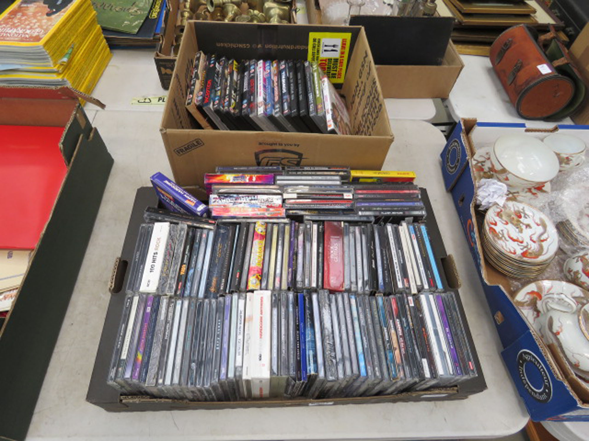 Two boxes containing DVDs and CDs