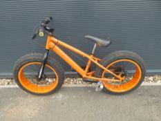 Large wheeled orange childs bike