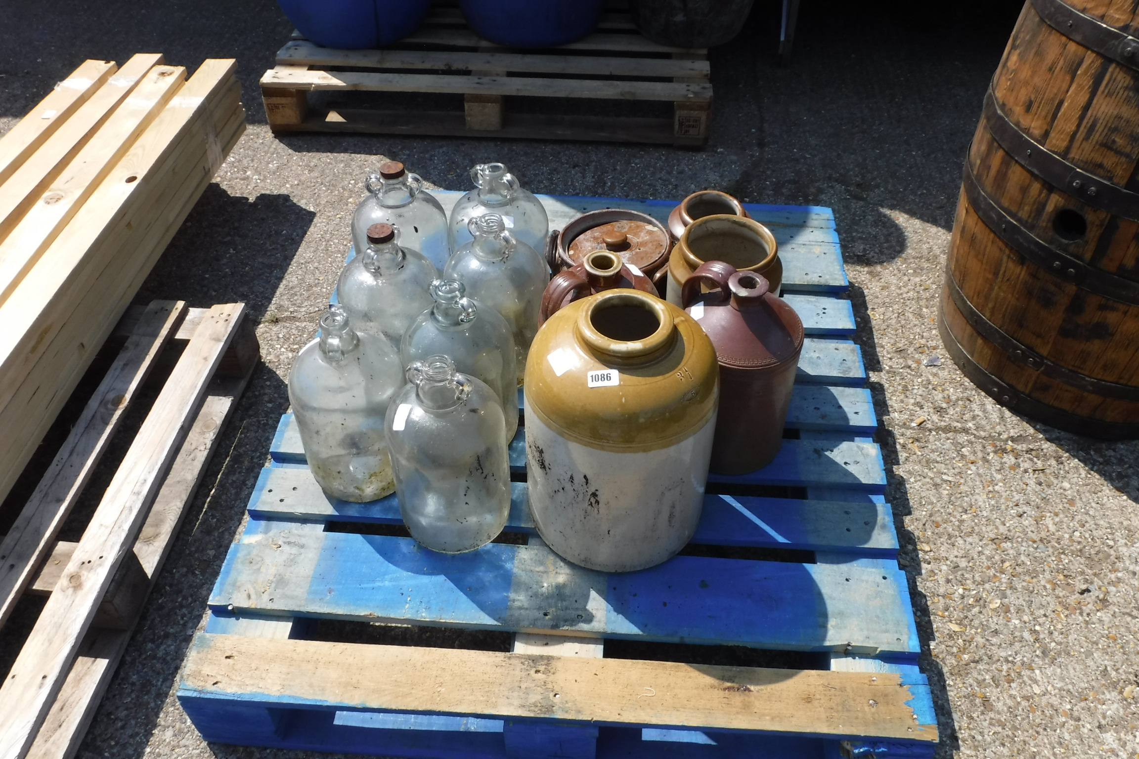 Selection of glass bottles and pottery jars on pallet