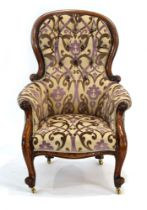 A Victorian mahogany and button upholstered armchair with scrolled front legs on castors