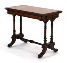 A Gillows side table, the walnut and ebonised top folding to reveal a baize covered games surface,