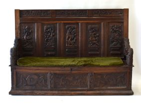 A heavily carved oak settle, the five- panelled back relief decorated with hunting scenes,