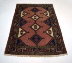 A Caucasian rug, the salmon ground with four medallians within a red and green foliate border,
