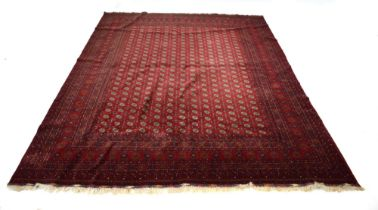A Turkoman carpet with a red ground, numerous medallians and fine geometric bands,