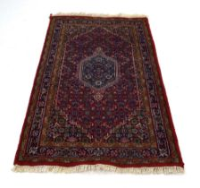 An Indian woolen carpet with a red ground,