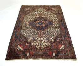 A Caucasian rug, the central medallian within a blue, cream and red ground,