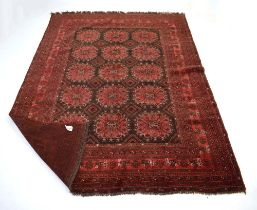 A Pakistani carpet, the red ground with fifteen medallians within matching bands,