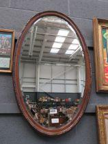 Oval bevelled 1920s mirror in oak frame
