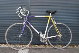 Purple, white and yellow racing cycle