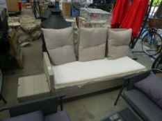 Rattan bench with beige cushions and footstool