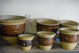 Set of 6 ceramic brown painted garden pots with leaf decoration