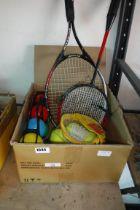 Box containing set of garden beach boules, tennis balls, shuttlecocks, 2 badminton rackets and