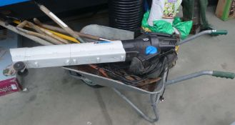 Wheelbarrow containing MacAllister leaf blower, forks, bulb planter, and weeder