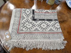 Woven rug with cream ground and geometric pattern