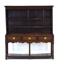 An 18th century oak dresser, the three tier plate rack over three drawers and a gallery,