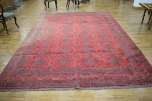 A 20th century woolen rug, the red ground with repeated motifs within matching borders,