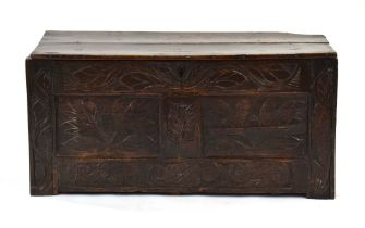 A late 17th/early 18th century oak coffer, the florally carved front with two panels,