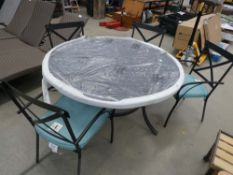 Large circular aluminium garden table on matching supports with 4 matching chairs and blue cushions