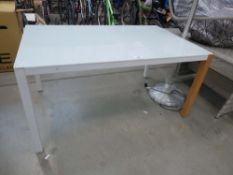 White glass top table on harlequin supports