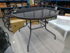 Smoked glass circular garden table on brown supports