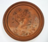 A terracotta roundel moulded with a ladies profile with ribbons in her hair,