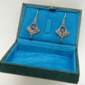 Pair of yellow gold and silver flared drop earrings set with blue sapphire gemstones and diamonds.