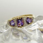 A Victorian-style dress ring set with amethysts and diamonds in 9ct yellow gold.
