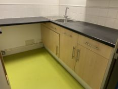 Small Kitchen area with cupboards, sink and tap.