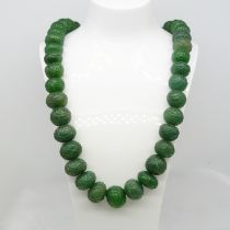 A large and weighty 890.00 ct earth-mined carved graduated emerald bead necklace with patterned cord