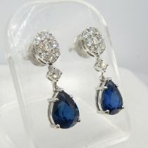 An exciting pair of pear shape sapphire and diamond cluster drop earrings in 18ct white gold