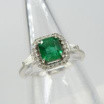 A square emerald ring with a diamond halo and tapered baguette diamond shoulders in 18ct white gold