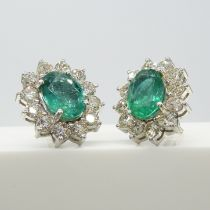 A striking pair of 18ct white gold 3.15 carat emerald and 2.40 carat diamond cluster stud earrings