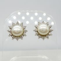 A pair of 9ct white gold cultured pearl and diamond halo stud earrings, boxed