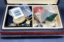 A wooden jewellery box with a selection of costume jewellery inside