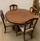 A dining table with turned legs and brass castors with four dining chairs and three leaf's (H74cm