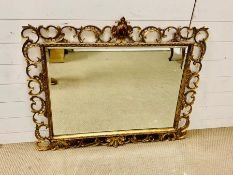A Giltwood composition mirror with rectangular plate and scrolling border. (104 cm x 90 cm)