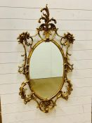 A Continental giltwood oval wall mirror with foliate themed scrolling borders.(70 cm x 130cm)