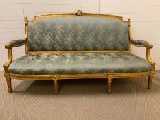 A Louis XVI style settee, foliate carved back, padded scroll down swept arms and stuffed over seat