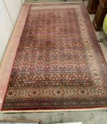 A red ground rug with centre square and boarder (353cm x 250cm)