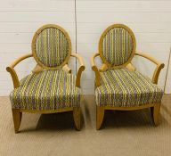 A pair of open armchairs on oak frames and circular backs (66 cm wide x 98 cm high and seat height